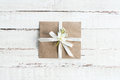 Top view of envelope with flower and ribbon on white wooden tabletop