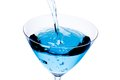 Top of view of filling a glass with blue cocktail tilted and bubbles on white background Stock Image