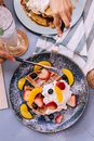 Top view of Fresh baked Pancakes topping with strawberry, orange, blueberry and whip cream with hands cut Royalty Free Stock Photo