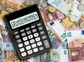 German word GRUNDEINKOMMEN basic income written on display of pocket calculator against cash money on table Royalty Free Stock Photo
