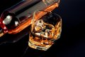 Top of view of glass of whiskey near bottle on black table with reflection time relax whisky Stock Photo