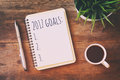Top view 2017 goals list with notebook, cup of coffee