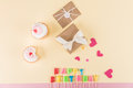 Top view of happy birthday lettering, envelopes with ribbons and hearts symbols on pink Royalty Free Stock Photo