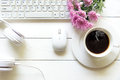 Top view headphones on white desk and computer with pink flower and copyspace area for a text and Cup of coffee beside headset. Royalty Free Stock Photo