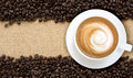 Top view of hot cappuccino with coffee beans on burlap backgroun Royalty Free Stock Photo