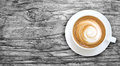Top view of hot coffee cappuccino in a white ceramic cup on gray Royalty Free Stock Photo