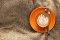 Top view hot latte in orange cup with floral pattern in foam on burlap background Royalty Free Stock Photo