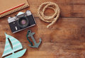 Top view image of blank notebook, wooden sailboat, nautical rope and camera. travel and adventure concept. retro filtered image Royalty Free Stock Photo