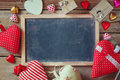 Top view image of colorful heart shape chocolates, fabric hearts, gift boxes and chalk board on wooden table