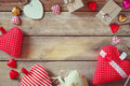 Top view image of colorful heart shape chocolates, fabric hearts and gift boxes on wooden table