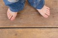 Top view of jeans and feet from a little girl close up Royalty Free Stock Photography