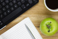 Top-view of keyboard, apple and writing equipment Stock Image