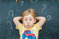 Top view of a little blond kid boy with question mark on blackboard. Concept for confusion, brainstorming and choice