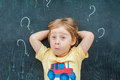 Top view of a little blond kid boy with question mark on blackboard. Concept for confusion, brainstorming and choice Royalty Free Stock Photo