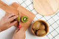Top view man hands slice fresh Kiwi fruit on chopping board Royalty Free Stock Photo