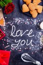Top view meringue cream lettering Love you on the black stone background with ingredients, flower, gift box with cookies and decor Royalty Free Stock Photo