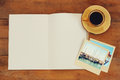 Top view of open blank notebook and travel polaroid photographs next to cup of coffee over wooden table. ready for mockup. retro f Royalty Free Stock Photo