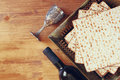 Top view of passover background. wine and matzoh (jewish passover bread) over wooden background. Royalty Free Stock Photo