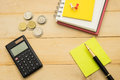 top view. pen putting on yellow post-it note and have black calculator, coin, pin and more post-it note putting on notebook. wood Royalty Free Stock Photo