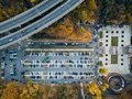 Top view photo of parking lot near bridge of road junction and city park taken by drone Royalty Free Stock Photo