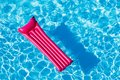 Pink inflatable mattress floating on water surface Royalty Free Stock Photo