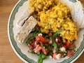 Plate with red lentil, tomato salad and slices of steamed pork