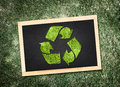 Top view of recycle symbol on blackboard with desaturated green grass background eco concept Stock Images