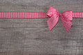Top view of a red checked ribbon decoration on wooden background old for christmas birthday voucher coupon present or gift Royalty Free Stock Photo