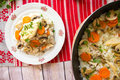Top view of rice with chicken and vegetables on plate and in skillet Royalty Free Stock Photo
