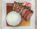 Top view of roasted duck and red pork with rice on white square plate on wooden table Stock Images