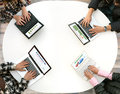 Top View of Rounded Desk with Four Laptops and People Hands Typing on Keyboard Royalty Free Stock Photo