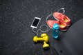 A top view of sportive accessories for gym training. Sport shoes, dumbbells, bottle, and a white phone on a black