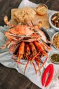 Top view of steamed Flower Crabs and Grilled Prawns Shrimps with Crab Cracker on paper with other seafoods in background Royalty Free Stock Photo
