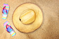 Top view of straw hat and flip flops on beach sand Royalty Free Stock Photo