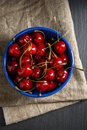 Top view: sweet cherry in blue bowl on black slate stone Royalty Free Stock Photo