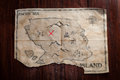 Top view to vintage fake crumpled treasure map on wooden table. Fake pirate handmade map with red cross as place of Treasure chest Royalty Free Stock Photo