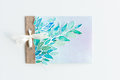 Top view of watercolor invitation with leaves and ribbon isolated on white