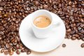 Top of view of white cup with espresso coffee near coffee beans over wood table Stock Photography
