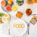 Top view white plate with Food word lettering by vitamin pills on the served wooden table with breakfast meal. Pill instead of foo Royalty Free Stock Photo