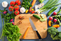 Top view of woman cooking healthy food: cutting vegetable ingred