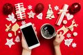 Top view of a woman holding a phone in one hand and a cup of coffee in another hand on red background. Christmas decorations and Royalty Free Stock Photo