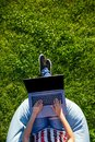 Top view. Woman working on laptop pc computer with blank black empty screen to copy space in park on green grass Royalty Free Stock Photo
