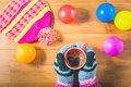 Top view women`s hands, gloves, Silk hat, colored balls and a cup of coffee on wood table. Royalty Free Stock Photo