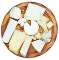 Top view of wooden plate with various cheeses Royalty Free Stock Photo