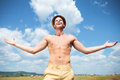 Topless man laughing outdoor with arms wide open young posing and a big thankful smile while looking at the sky Royalty Free Stock Photography