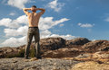 Topless man relaxed stands on the mountain strong and looks over horizon Royalty Free Stock Images