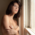 Topless by window an image of a young woman a covering her chest with her arms Stock Image