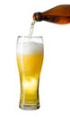 Topping up light beer from bottle to glass isolated on white Royalty Free Stock Photo