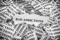 Torn bad addictions pieces of paper with the words concept image black and white close up Royalty Free Stock Image