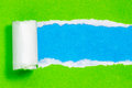 Torn green color paper on blue  background Royalty Free Stock Images
